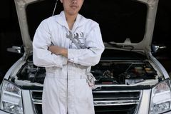 Portrait of professional young mechanic man in uniform holding wrench against car in open hood at the repair garage. Royalty Free Stock Photos