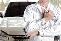 Portrait of professional young mechanic man in uniform holding wrench against car in open hood at the repair garage. Stock Photo