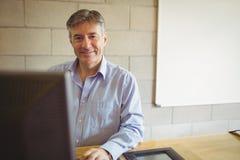 Portrait of professor sitting on desk Royalty Free Stock Photos