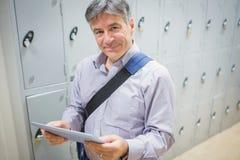 Portrait of professor using digital tablet in locker room Royalty Free Stock Photos