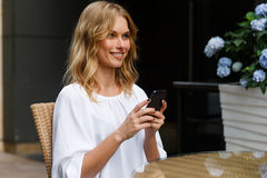 Portrait in profile of attractive blond girl with mobile phone Royalty Free Stock Photo