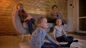 Portrait in profile of small caucasian girls watching movie attentively and talking with each other in cosy home stock video