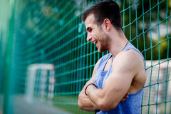 Portrait in profile of smiling sportsman with bare muscular arms Royalty Free Stock Photo