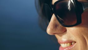 Portrait, profile of a smiling woman in sunglasses. sunbeams reflected in glasses. against the blue sea
