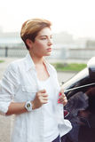 Portrait in profile of stylish young woman in white shirt. Portrait in profile of caucasian stylish young woman in white shirt on street background Royalty Free Stock Photos