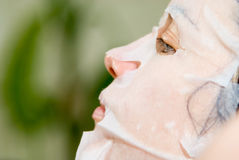 Portrait in Profile woman applying rejuvenating facial mask on h Stock Image