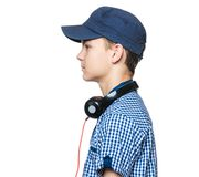 Teen boy with cap and headphones. Portrait profile of young student with cap and headphones, isolated on white background Stock Images