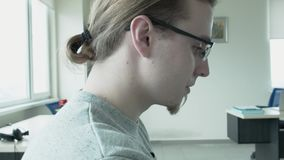 A portrait of a programmer wearing glasses and a tail, which was busted at work. He drops his head down. The camera from. The close-up of the face falls into stock footage
