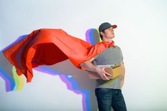 Sublime postman expressing heroism and holding parcel. Portrait of proud courier keeping package while wearing red cape. Honor and delivery concept Stock Images