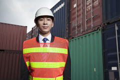Portrait of proud engineer in protective workwear standing in a shipping yard Royalty Free Stock Photo