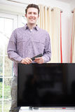 Portrait Of Proud Man With New Television At Home Stock Photos