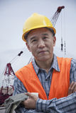 Portrait of proud worker with arms crossed in protective workwear outside in a shipping yard, crane in the background Stock Photos