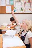 Portrait of a pupil raising her hand Stock Images
