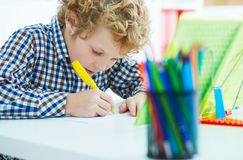 Portrait of pupil in school class taking notes during writing lesson. Education, childhood, homework and school concept. Portrait of pupil in school class Royalty Free Stock Photos