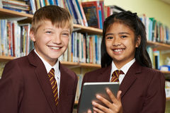 Portrait Of Pupils Wearing School Uniform Using Digital Tablet I. Pupils Wearing School Uniform Using Digital Tablet In Library Stock Images