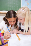 Portrait of pupils working together on an assignment Royalty Free Stock Images