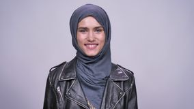 Portrait of pure and jolly caucasian girl in hijab laughing and smiling sincerely on gray background. Portrait of pure and jolly caucasian girl in hijab who stock footage