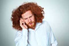Portrait of puzzled man talking on the phone a gray background Stock Photos