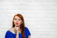 Facial Expressions Of Young Redhead Woman On Brick Wall. Portrait of puzzled woman having doubts, doubtful redhead girl thinking. Youth culture with female teen Royalty Free Stock Image