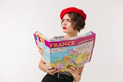 Portrait of a puzzled woman wearing red beret. Holding travel map guide isolated over white background Stock Images