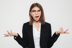 Portrait of a puzzled young businesswoman in suit. And eyeglasses gesturing with hands isolated over white background royalty free stock photos
