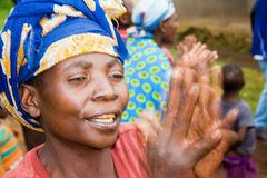 Portrait of pygmy woman. KISORO, UGANDA - DECEMBER 31, 2013: An unidentified pygmy woman claps her hands and sings Royalty Free Stock Photos