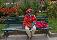 Portrait of Quechua man Sacred valley,Peru. An indigenous Peruvian man dressed in colorful traditional clothing sitting in the central plaza, Ollantaytambo, Peru Stock Photos