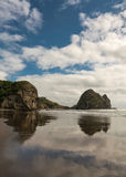 Portrait of Rabbit Rock at Piha Beach. Auckland, New Zealand - March 2, 2017: Closeup of Rabbit rock is mirrored on wet sandy Piha Beach under blue cloudy sky royalty free stock photos