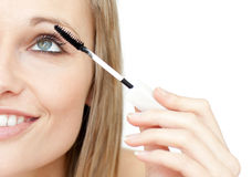 Portrait of a radiant woman putting mascara Royalty Free Stock Photos
