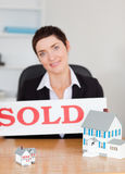 Portrait of a real estate agent. With a sold panel and houses miniatures in her office Royalty Free Stock Photos