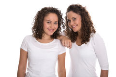Portrait of real twin sisters isolated over white. Royalty Free Stock Image
