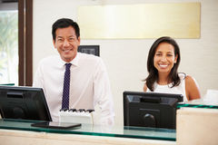 Portrait Of Reception Staff At Hotel Front Desk Stock Image