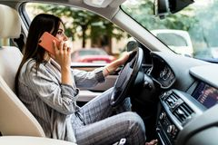 Portrait of woman driver talking her mobile phone while driving car. royalty free stock photos
