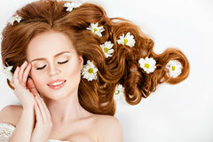 Portrait of red-haired beautiful and gentle girl with daisies in stock photography