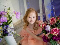 Red-haired beautiful girl with bouquet of flowers in the studio. Spring. Portrait of a red-haired beautiful girl with freckles on her face with a bouquet of Stock Photo