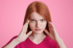 Portrait of red haired freckled female tries to concentrate, has. Serious expression, keeps hands on temples, has headache, wears bright pink sweater, poses in Royalty Free Stock Photo