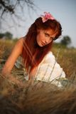 Portrait of the red-haired girl. Sitting in a grass stock photography