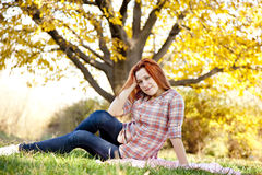 Portrait of red-haired girl in the autumn park. Stock Images