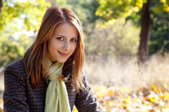 Portrait of red-haired girl in the autumn park Royalty Free Stock Photos