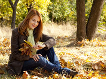 Portrait of red-haired girl in the autumn park Royalty Free Stock Photo
