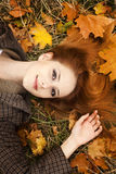 Portrait of red-haired girl in the autumn park. Stock Photos