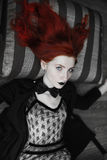 Portrait of red-haired girl in bow tie on a dark background, gothic style Royalty Free Stock Photo