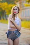 Portrait of red-haired girl with bright makeup. In shiny shorts and a white transparent blouse Stock Photo