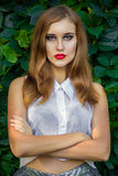 Portrait of red-haired girl with bright makeup. In shiny shorts and a white transparent blouse Royalty Free Stock Photo