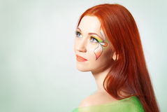 Portrait of red-haired girl with flower painted on his face Royalty Free Stock Photo