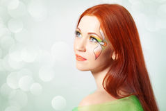 Portrait of red-haired girl with flower painted on his face Stock Photos