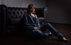 Portrait of a red-haired girl in a jeans shirt and jeans sitting at the black sofa on the floor. Horizontal photo Royalty Free Stock Photo