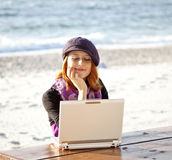 Portrait of red-haired girl with laptop at beach. Royalty Free Stock Photos