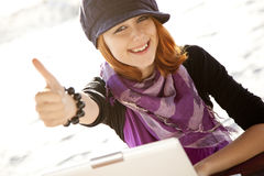 Portrait of red-haired girl with laptop at beach. Royalty Free Stock Image