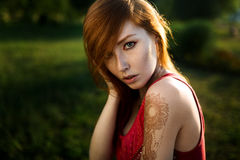 Portrait of a red-haired girl with a mehendi on her shoulder against a background of greenery in the sunset light. Close-up portrait of a redheaded young girl Stock Photography